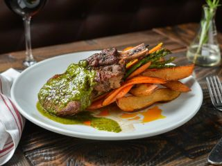 Cowgirl Steak-Frites, a cowgirl rib-eye with crispy wedge cut fries, asparagus and baby carrots--all topped with the chef's special chimichurri--at Brewology in Port Jefferson. (Credit: Daniel Brennan)